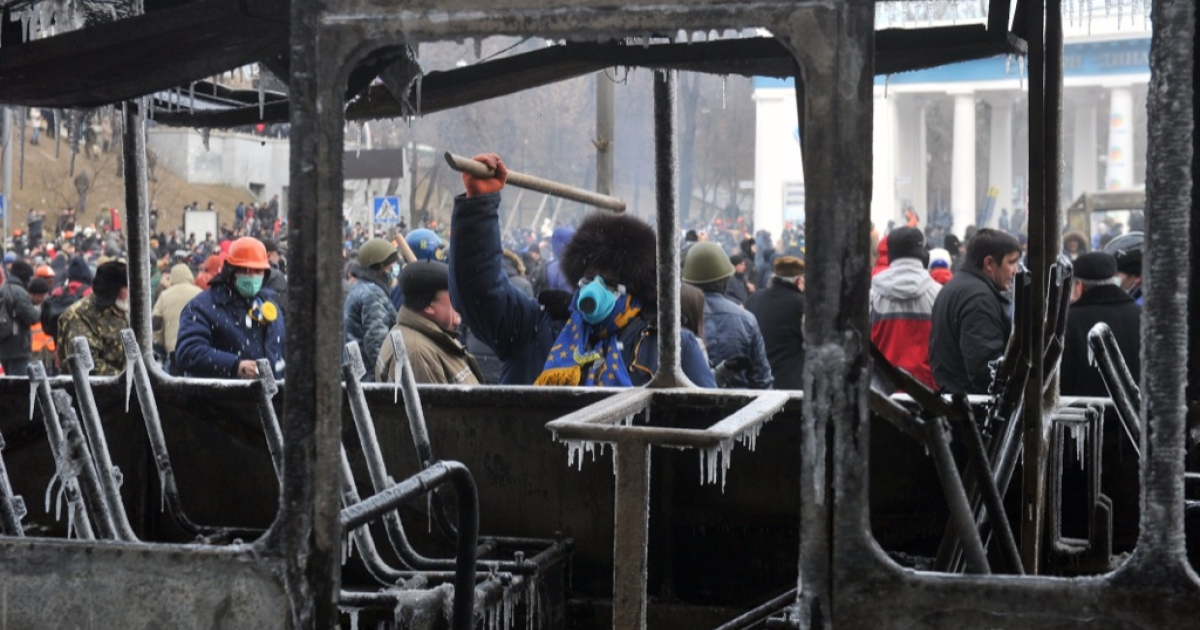 Protesters stand behind a burned bus during clashes with police in central Kyiv on Jan. 20, 2014. EU foreign ministers deplored the violence, saying the government was at fault for passing a package of repressive laws in an effort to tame pro-EU demonstrations.</p>