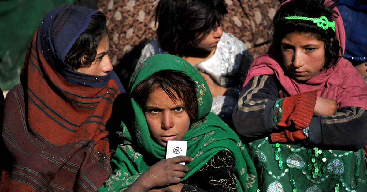 Afghan children wait for relief supplies at a refugee camp on the outskirts of Kabul. Authorities said a girl, possibly as young as eight, tried to carry out a suicide bombing attack on January 5, 2014.</p>