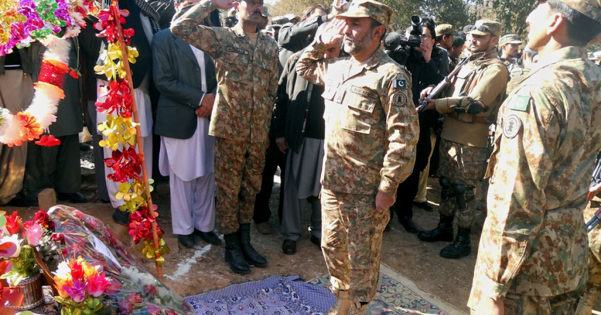 Pakistani army personnel salute after placing flowers at the grave of student Aitzaz Hassan in Hangu, Khyber Pakhtunkhwa, on January 11, 2014. Hassan, 15, sacrificed his life to stop a suicide bomber, saving the lives of hundreds of students, and has been handed the country's highest award for bravery.</p>