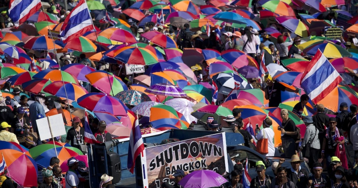 Demonstrators wave flags and hold sun umbrellas on Jan. 13, the first day of the