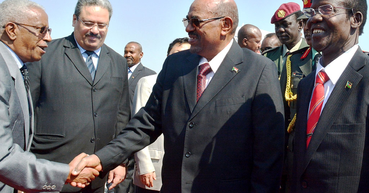 Sudan's President Omar al-Bashir (C) salutes official as he is welcomed by South Sudan's Vice-President James Wani Igga (R) upon his arrival at Juba's airport on January 6, 2014 before meeting at the presidential palace.</p>