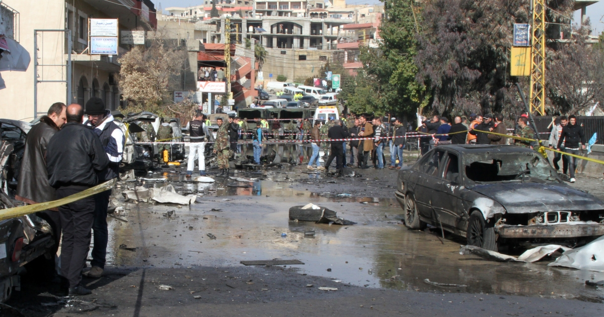 Lebanese security forces and civilians stand at the scene of a car bomb explosion that went off in front of the main government administration building in Hermel, near the border with Syria, on January 16, 2014.</p>