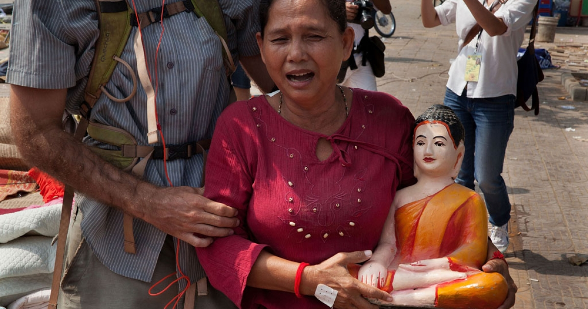 A woman carrying a statue of Buddha is escorted away from a camp set up by opposition party leaders at Freedom Park on Jan. 4, 2014 in Phnom Penh, Cambodia.</p>