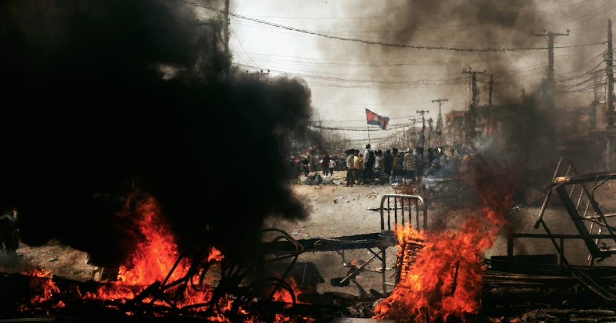 Protesters await police behind a burning barricade on January 3, 2014 in Phnom Penh, Cambodia. Dozens have been injured, and at least five people have reported dead after police broke up demonstrations by garment workers demanding wage increases. South Korea is now boasting a behind-the-scenes role in the crackdown.</p>