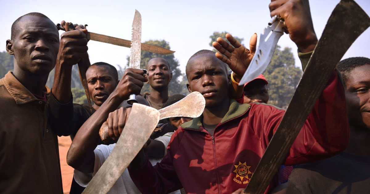 Men brandish machetes and knives to threaten muslim people in Bangui on January 12, 2014 as rival militiamen struck a truce Sunday and hugged each other in a neighborhood of the Central African Republic's capital on the eve of consultations aimed at replacing the president who resigned under international pressure.</p>