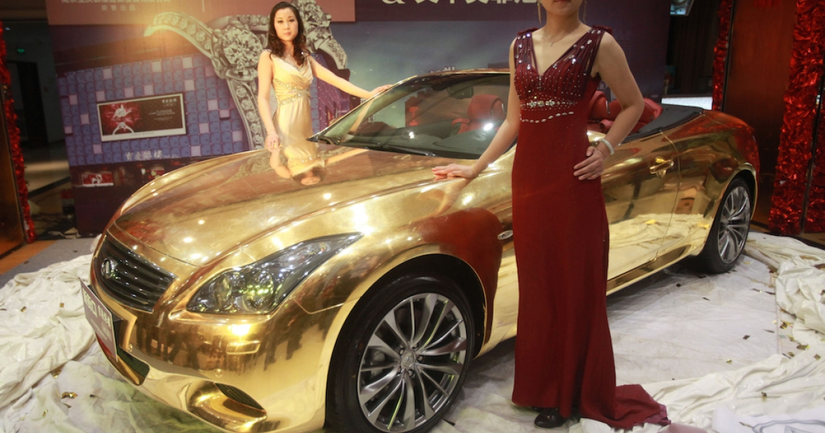 Models pose with a gold-plated Infiniti luxury sports car at a jewellery store in Nanjing. China is predicted to become the world's largest luxury goods market by 2020, but many of the country's wealthy are choosing to emigrate abroad, according to a new study.</p>