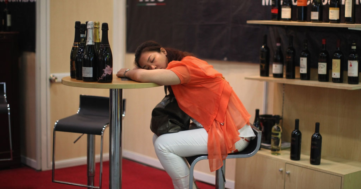 A woman sleeps after a red wine tasting during the Top Wine China 2012 convention on June 5, 2012 in Beijing, China.</p>