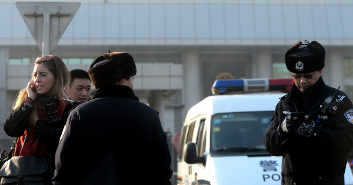 Chinese police stop a foreign journalist outside the trial of Xu Zhiyong on January 22, 2014, under strict security. Xu, one of China's most prominent anti-corruption activists, called for the government to publish the assets of officials. Today, the International Consortium of Investigative Journalists revealed extraordinary overseas wealth of Chinese elites.</p>
