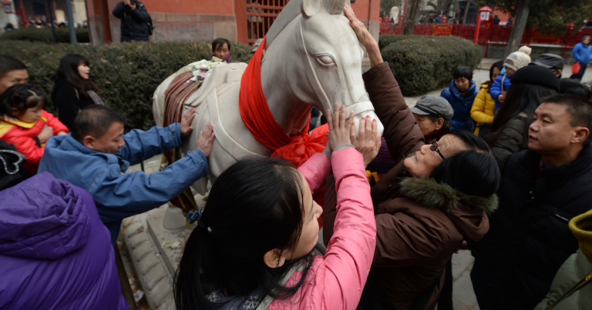 Chinese visitors to the Dongyue Temple in Beijing touch a white jade horse to bring them good luck in the coming year on Jan. 31, 2014.</p>