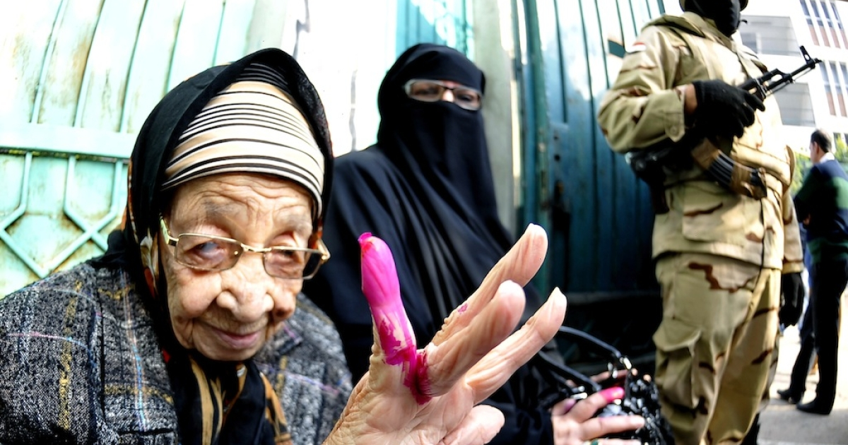 An Egyptian woman shows her ink-stained finger after casting her vote at a polling station during the second day of voting on a new constitution on Wednesday in the northern port city of Alexandria.</p>