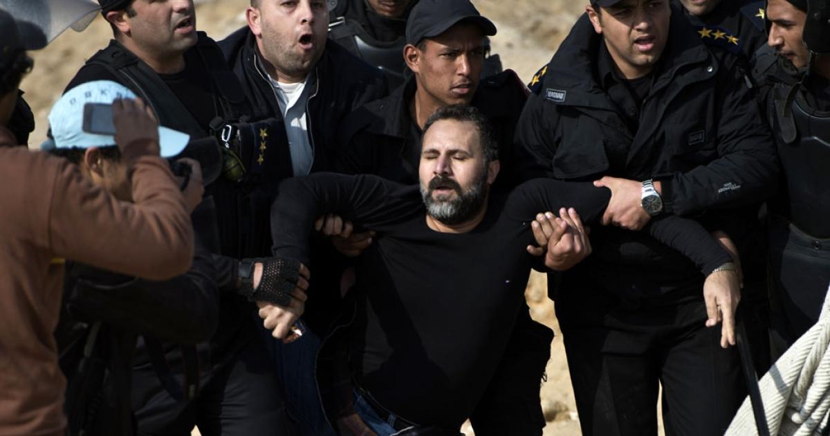 Egyptian policemen arrest a Mohamed Morsi supporter on January 8, 2014 in Cairo.</p>