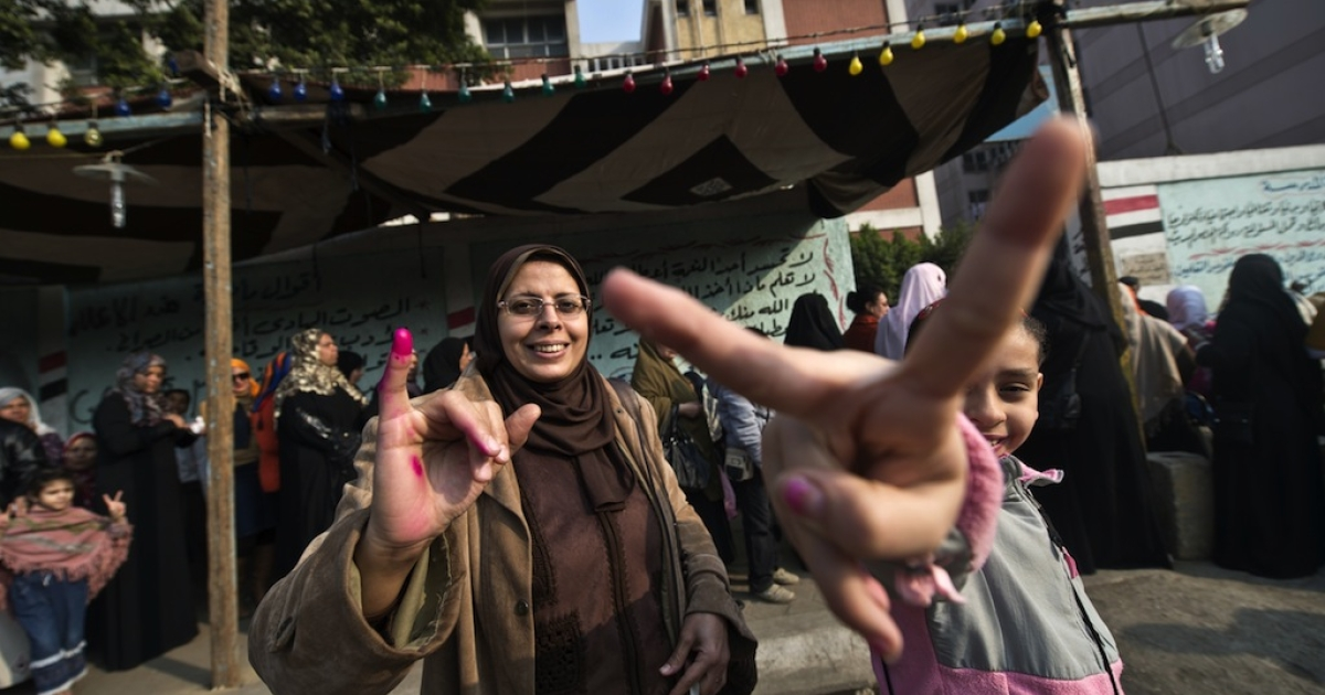 An Egyptian girl flashes the victory sign as her mother shows her ink-stained finger outside a polling station in Cairo on Tuesday.</p>