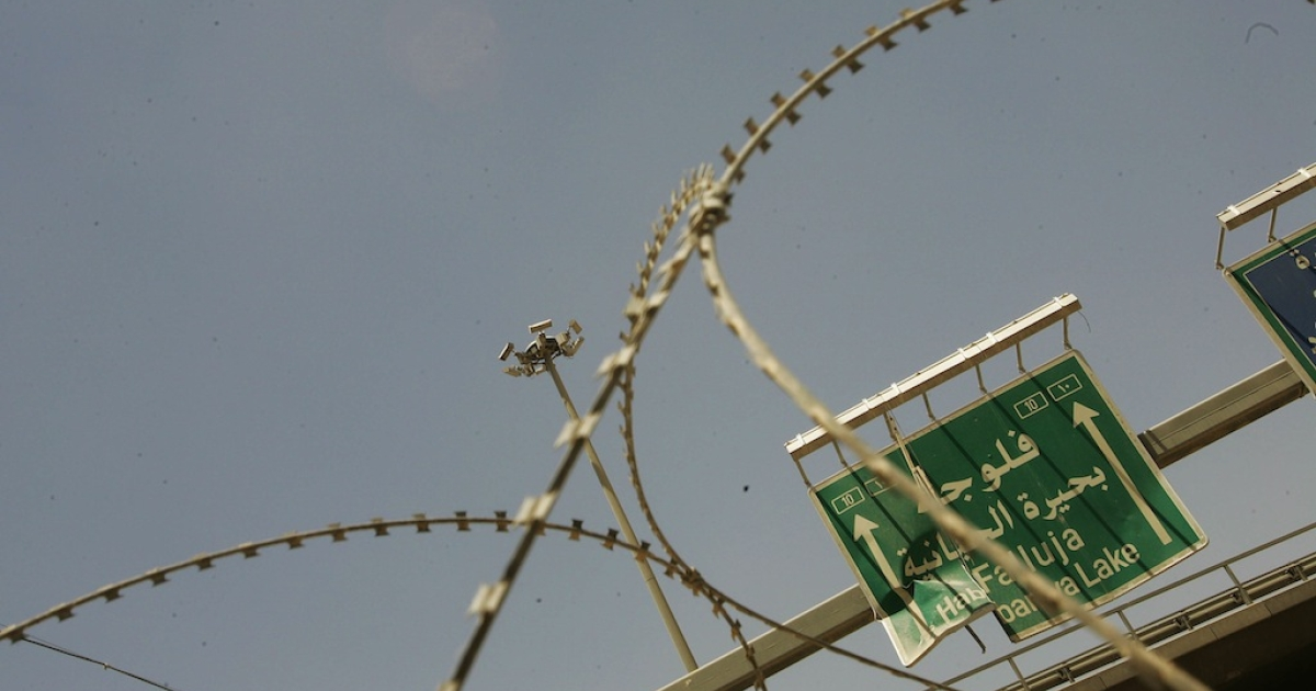 Razor wire marks the entrance to Entry Control Point 1, a US Marine guarded entry into the city June 25, 2005 in Fallujah, Iraq.</p>