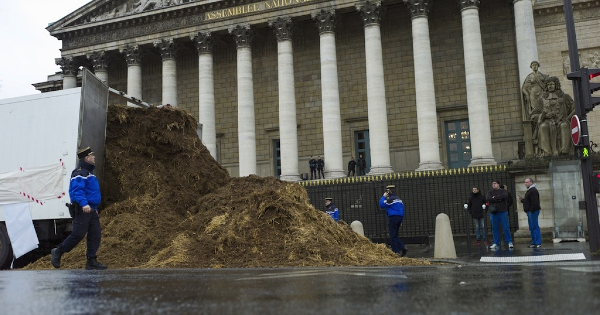 French police stand around a pile of horse dung that was dumped outside the national parliament building in Paris on Thursday.</p>