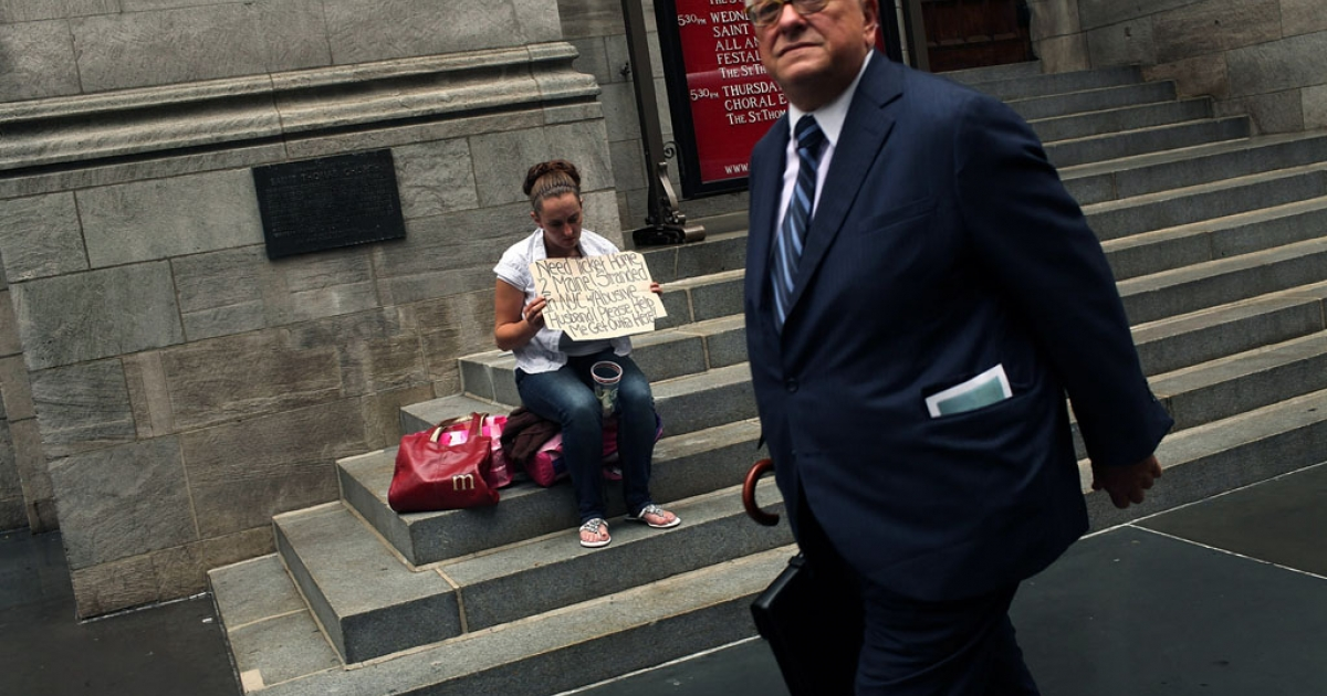 A businessman walks by a homeless woman holding a card requesting money in New York City.</p>