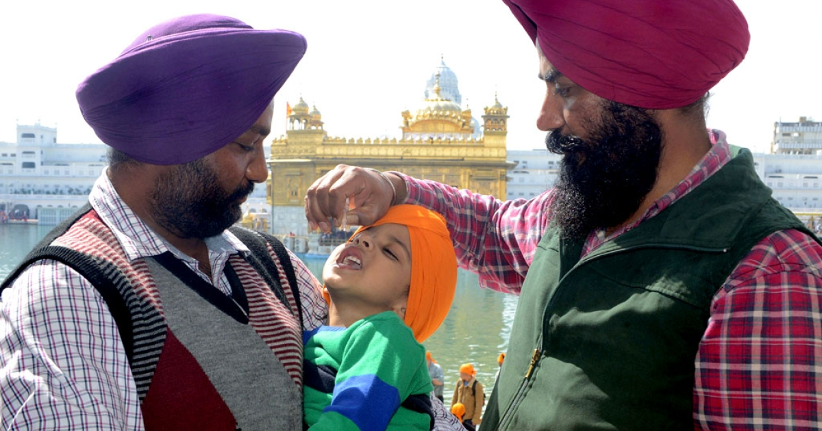 An Indian Sikh boy receives polio vaccination drops from a medical volunteer during an immunisation drive outside the Golden Temple in Amritsar on February 24, 2013.</p>