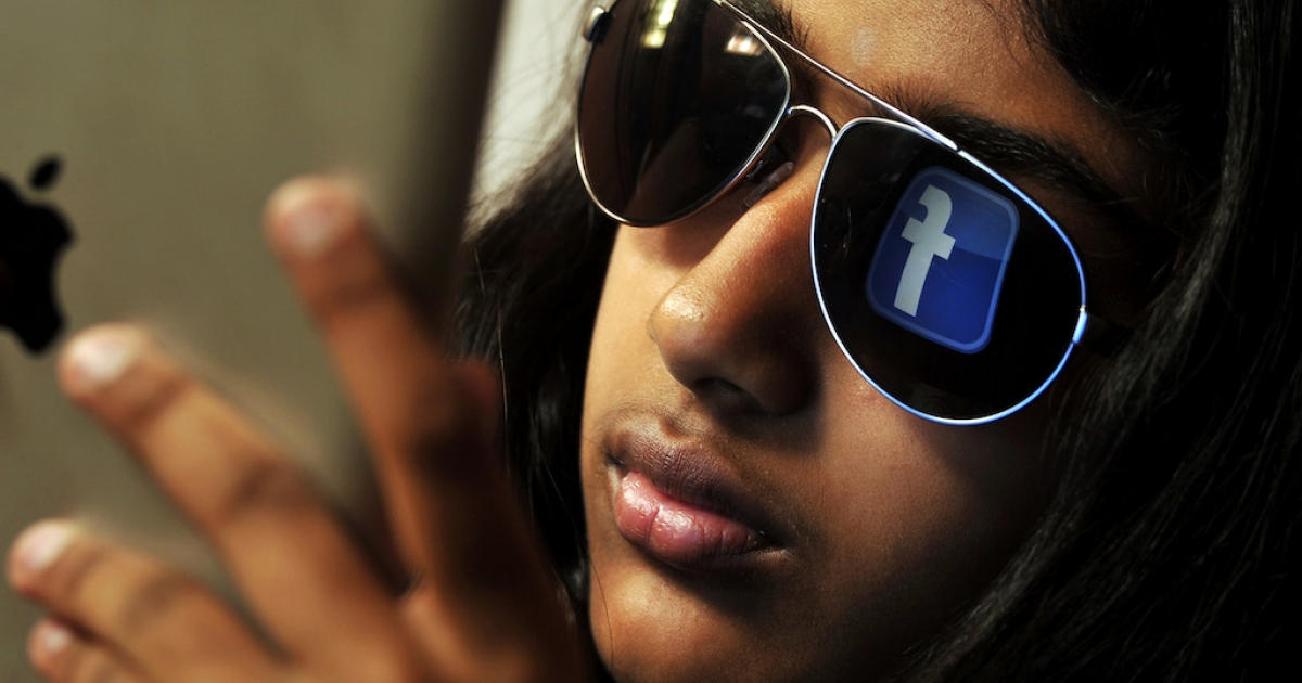 The Facebook logo is reflected in a young Indian woman's sunglasses as she browses on a tablet in Bangalore on May 15, 2012. Indians eager for US work visas are prime targets for con-artists.</p>