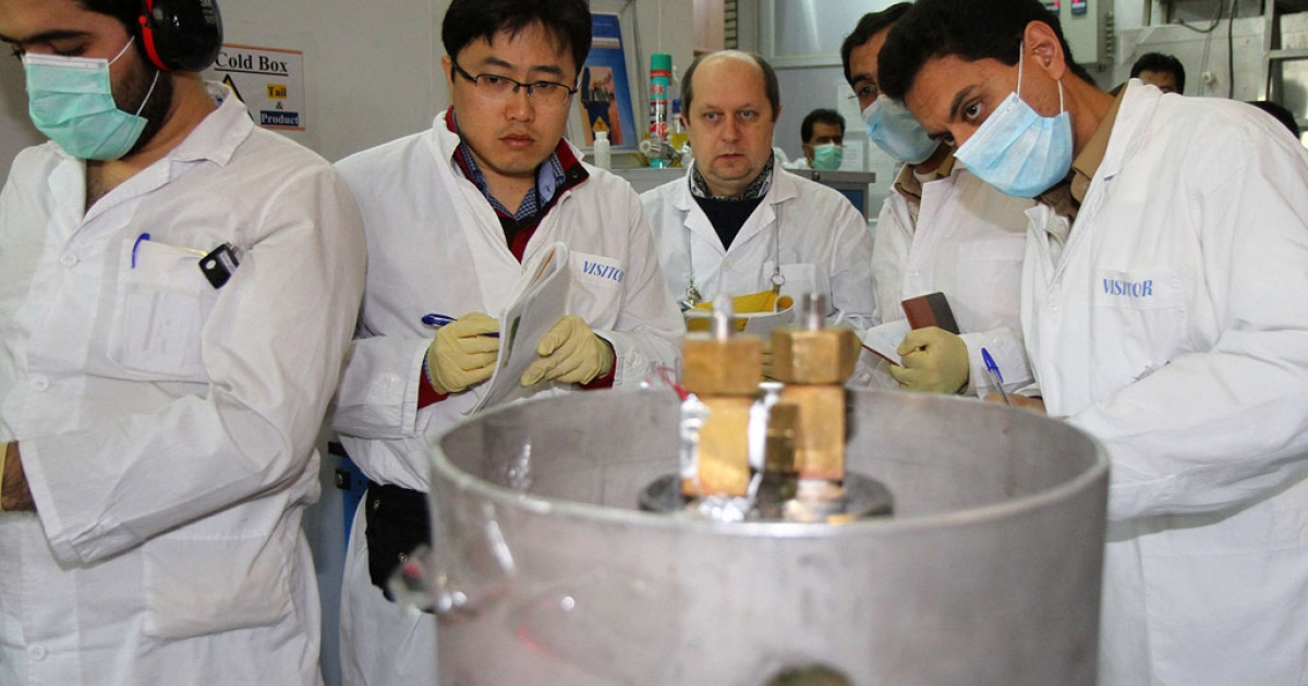 Unidentified International Atomic Energy Agency (IAEA) inspectors (2nd-3rd L) and Iranian technicians disconnect the connections between the twin cascades for 20 percent uranium production at nuclear power plant of Natanz, some 300 kilometers south of Tehran on January, 20, 2014.</p>