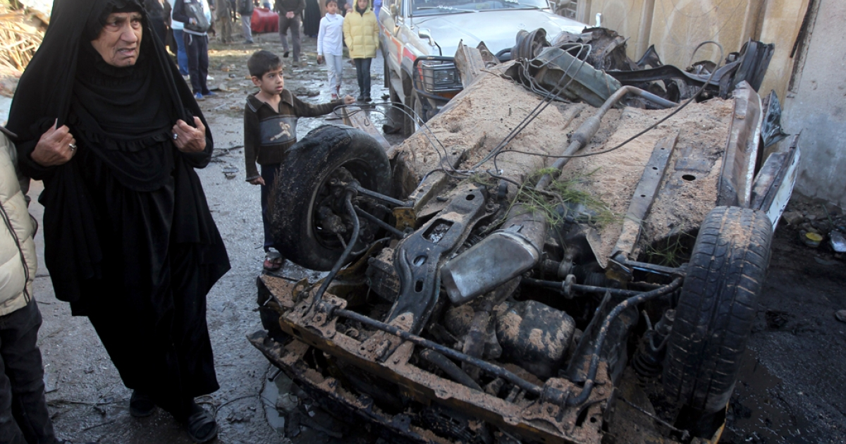 Iraqi civilians gather at the site of the aftermath of a car bomb explosion in the Shuala area of the Iraqi capital Baghdad on January 30, 2014.</p>