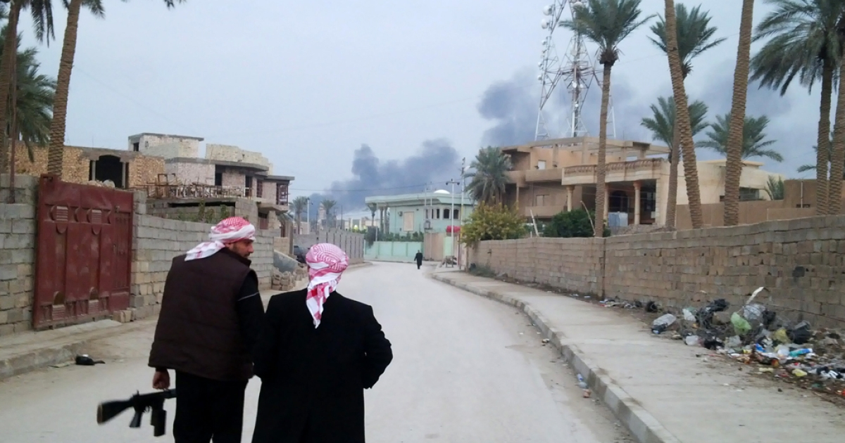 Armed tribesmen stand guard in a street as clashes rage on in the Iraqi city of Ramadi, West of Baghdad, on January 2, 2014. Iraqi special operations forces were fighting in the city of Fallujah, half of which is reportedly under the control of militants linked to Al Qaeda, their commander said.</p>