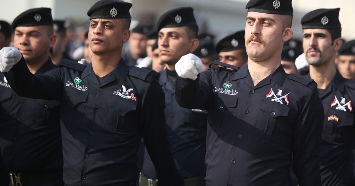 Iraqi policemen march during a ceremony marking police forces 92nd anniversary in the capital Baghdad on January 9, 2014.</p>