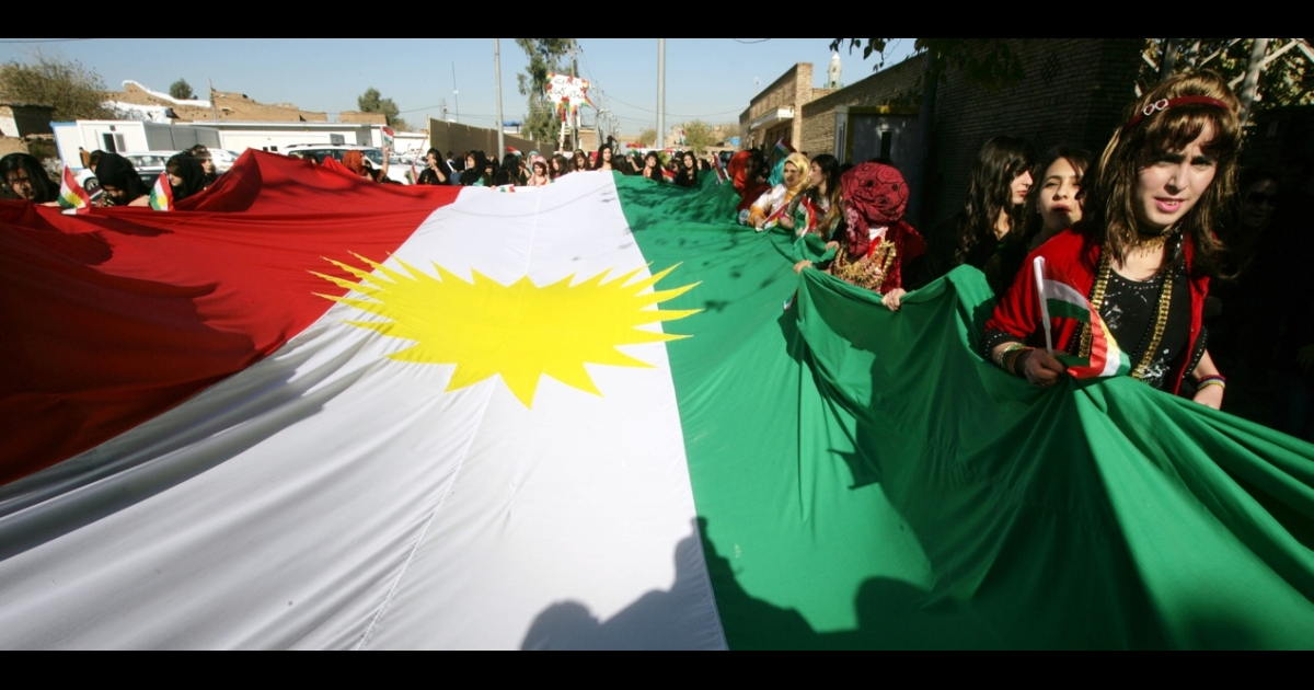 Iraqi Kurdish girls carry a large Kurdistan flag during the celebration of Flag day in the northern city of Erbil on Dec. 17, 2013.</p>