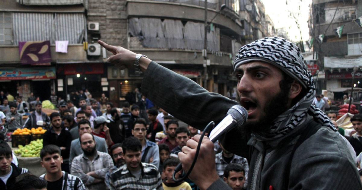 A member of the Islamic State of Iraq and the Levant (ISIL) speaks into a microphone urging people to join their fight against the regime, in the northern Syrian city of Aleppo on November 13, 2013. Syrian troops advanced on the Islamist-held northern village of Tal Hassel, prompting jihadist rebels in nearby Aleppo to call for mass mobilization to counter the offensive. AFP PHOTO/MAHMUD AL-HALABI</p>