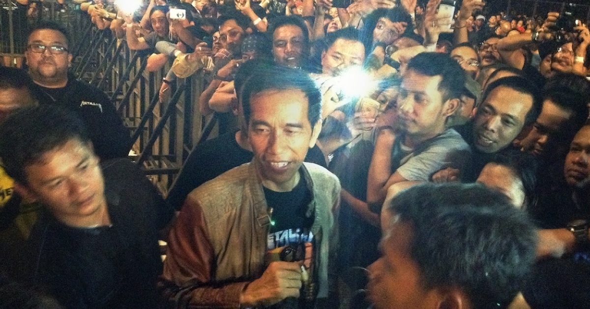 Jakarta Governor Joko Widodo (center, in black T-shirt and leather jacket), is mobbed by rock fans as he arrived to watch a Metallica concert at Jakarta's Bung Karno stadium on August 25, 2013. Polls give him a commanding lead in the Indonesian presidential election, although he has not yet agreed to run.</p>