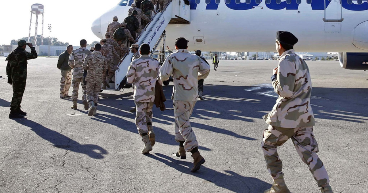 A batch of former rebels who have joined the ranks of the Libyan army board a plane in the capital Tripoli, heading to Italy on January 9, 2014, to receive training under a plan to rebuild the Libyan army.</p>