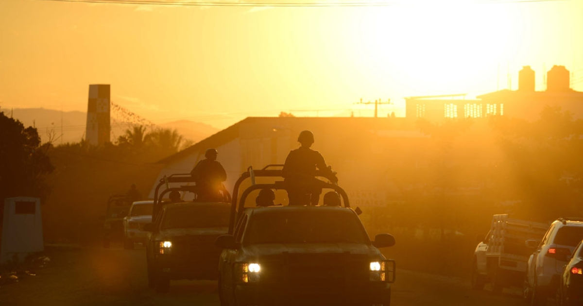 A convoy of Mexican soldiers patrol a road in Tepalcatepec, in Michoacan State, Mexico, on January 15, 2014, where government officials held a meeting with members of the Self-Protection Police.</p>