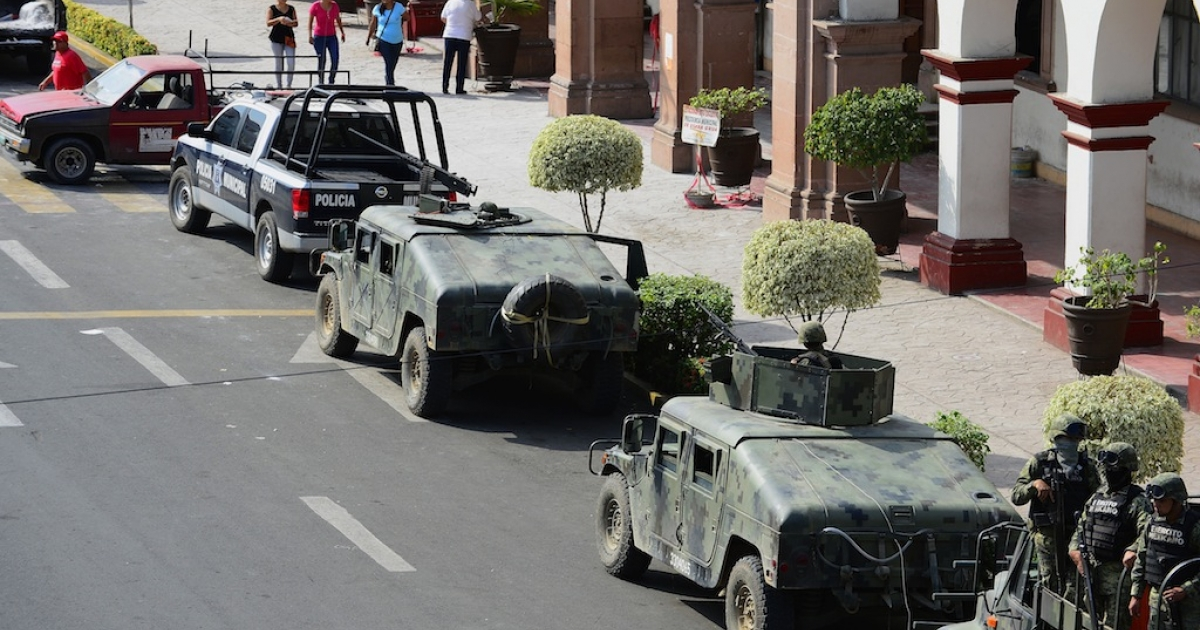 A convoy of army vehicles is parked outside the town hall of Apatzingan, a key stronghold of the Knights Templar cartel, in Michoacan state, Mexico, on Jan. 16, 2014.</p>