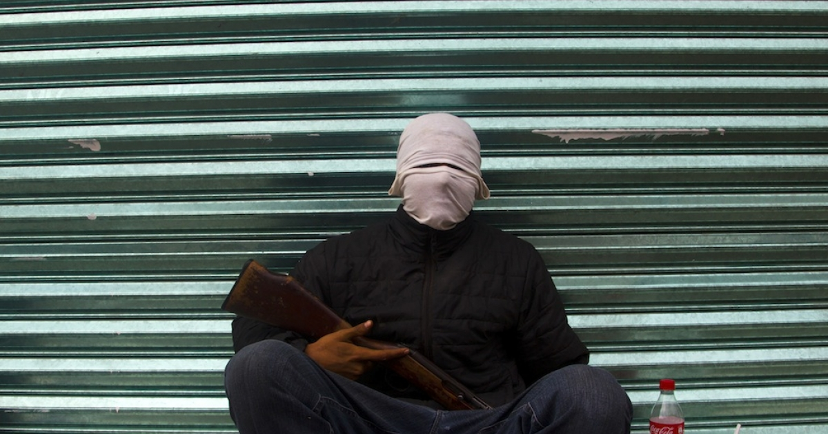 An armed member of a self-defense group sits on a street in the town of Uspero in Michoacan state, Mexico, on Jan. 16, 2014.</p>