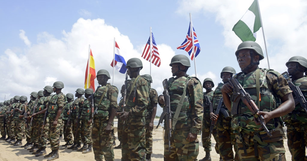 Nigerian soldiers march before flags of participating countries during a joint military exercise in 2013.</p>