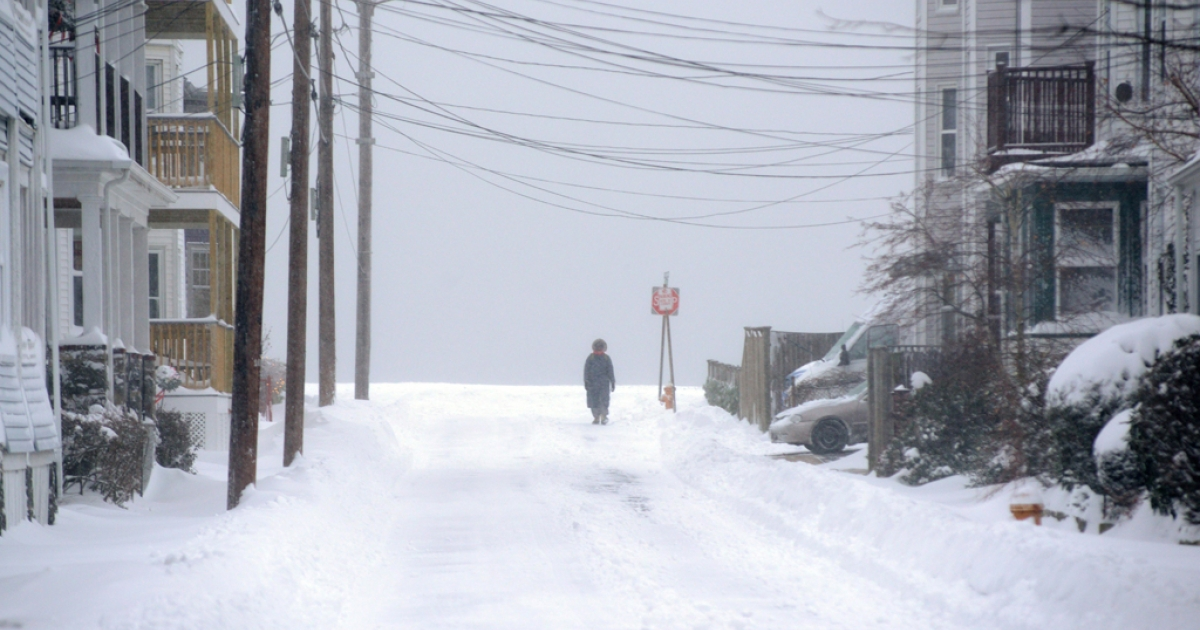 A woman walks down snowy Forrest Street after an overnight storm January 3, 2014 in Winthrop, Massachusetts.</p>