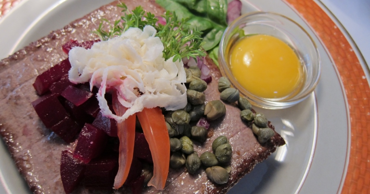 Classic smørrebrød: ground beer patty, capers, picked beets, cress, fresh horseradish and a raw egg yolk.</p>