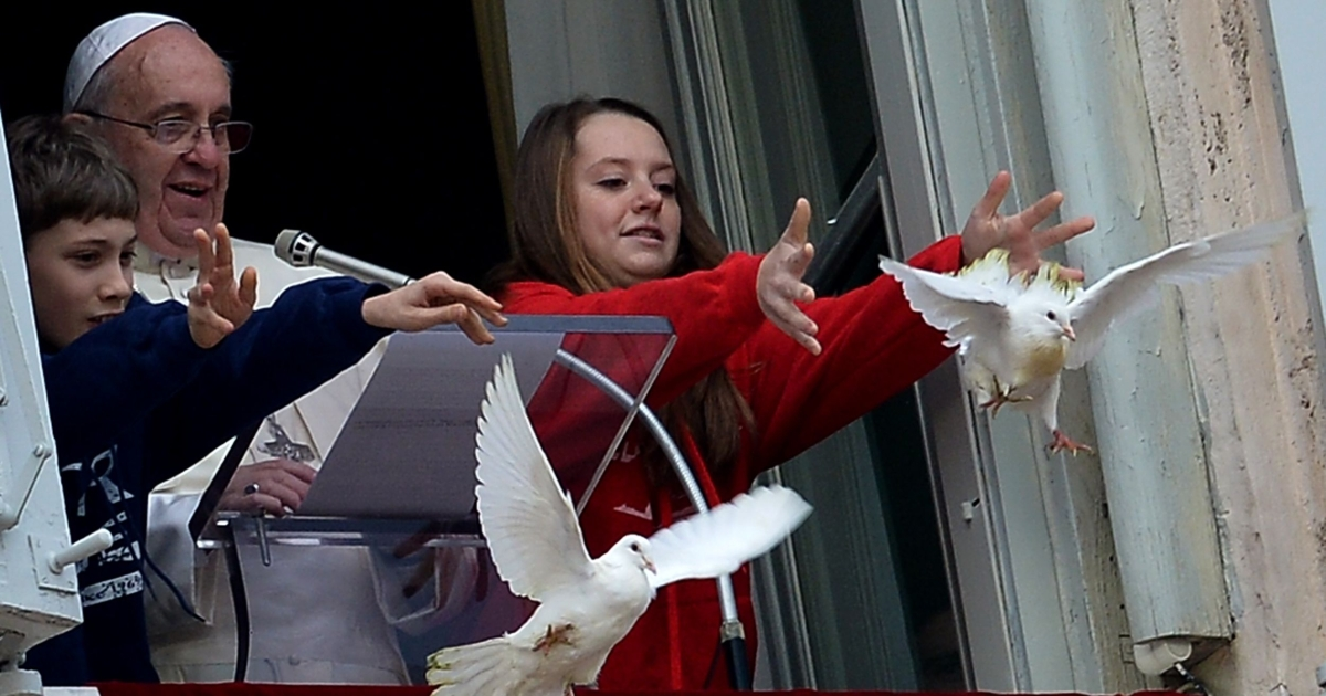 Children release white doves next to Pope Francis from the window of his private apartments during his sunday's Angelus prayer at St Peter's square on Jan. 26, 2014, at the Vatican. The doves were soon attacked by a crow and a seagull, horrifying some in the crowd below.</p>
