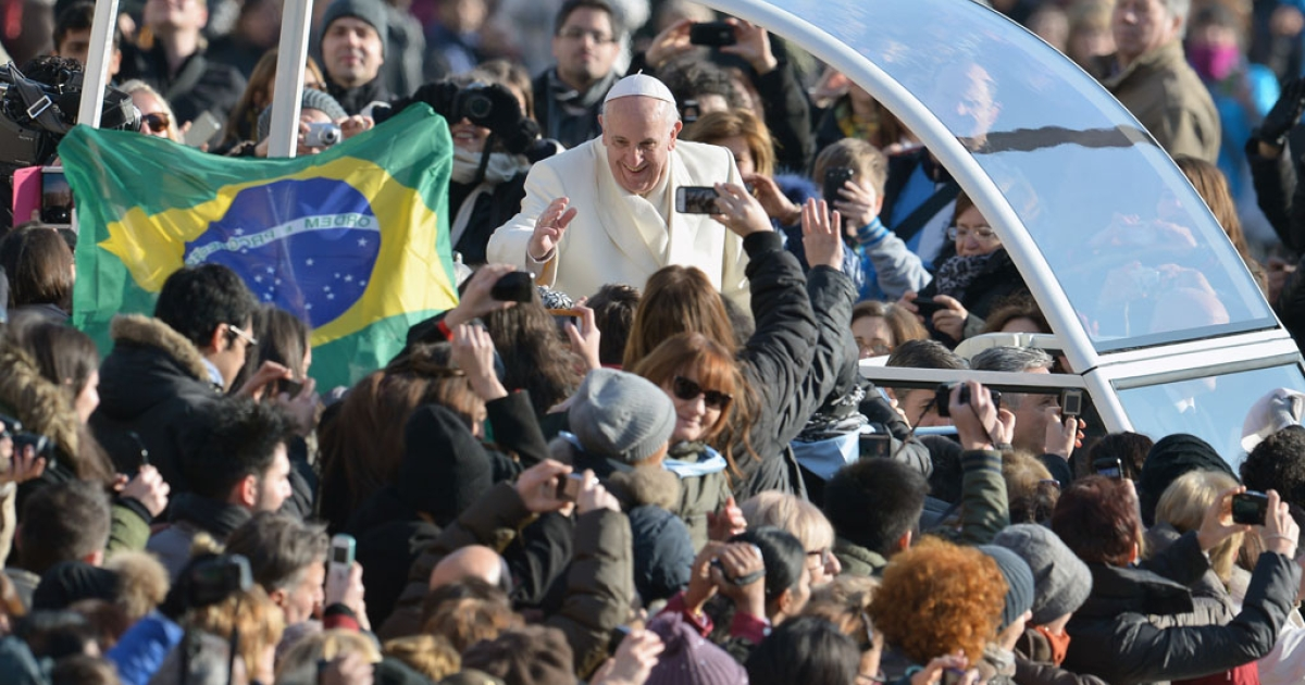 Pope Francis waves to the admirers as he arrives at St. Peter's Square at the Vatican for his weekly general audience on January 8, 2014.</p>