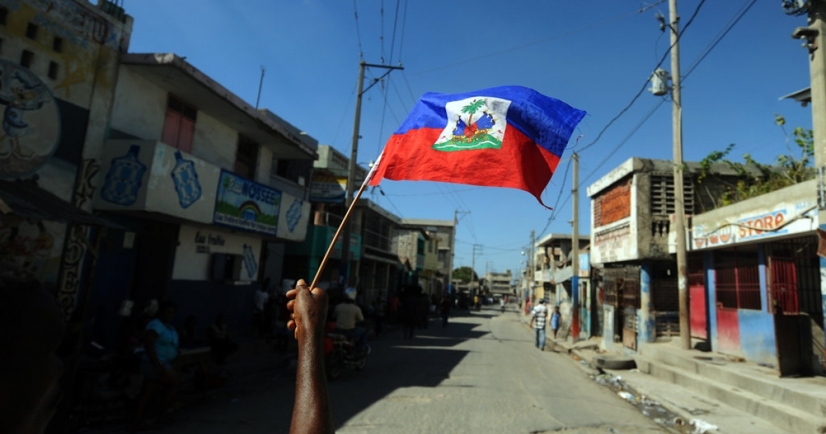 A man holds a Haitian flag as he takes part in a protest demanding that Haitian President Michel Martelly step down in Port-au-Prince on January 13, 2014. The protesters walked from one sector of the center of the capital to the parliament, where Martelly was to deliver a speech on the country's political and economic situation.</p>