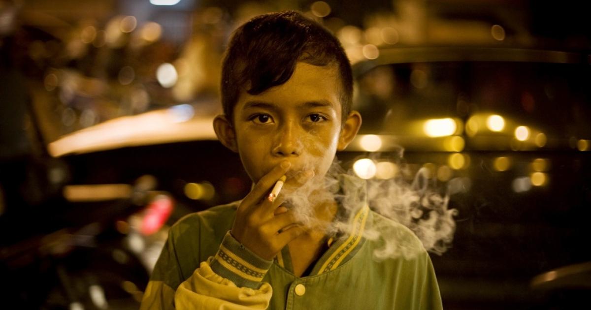 Rizki, age 15, smokes in the street in 2011 in Yogyakarta, Indonesia.</p>