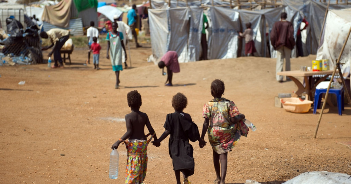 Three children walk through a spontaneous camp for internally displaced persons at the United Nations Mission to South Sudan (UNMISS) base in Juba,  on January 9, 2014.</p>