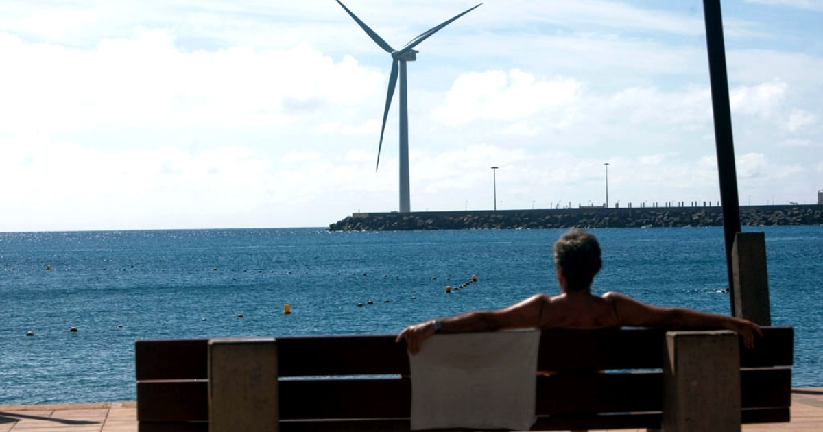 A woman sits on a bench in front of Spain's largest wind turbine, Arinaga. It's located on Gran Canaria in the Spanish archipelago of the Canary Islands.</p>