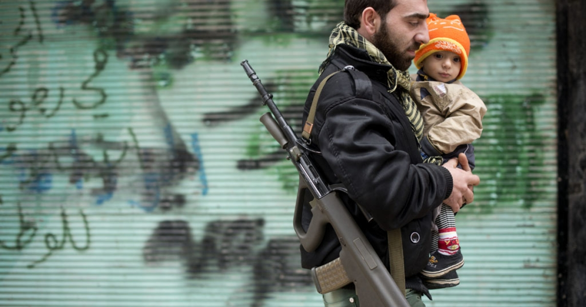 A rebel fighter carries his son after Friday prayers in the al-Fardos neighbourhood of Aleppo on December 7, 2012.</p>