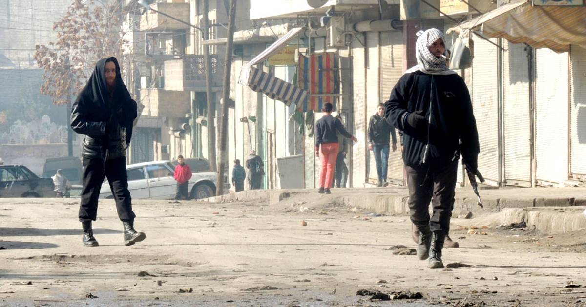 Rebel fighters, one holding a weapon, walk in a street on January 7, 2014 in the northern Syrian city of Aleppo.</p>