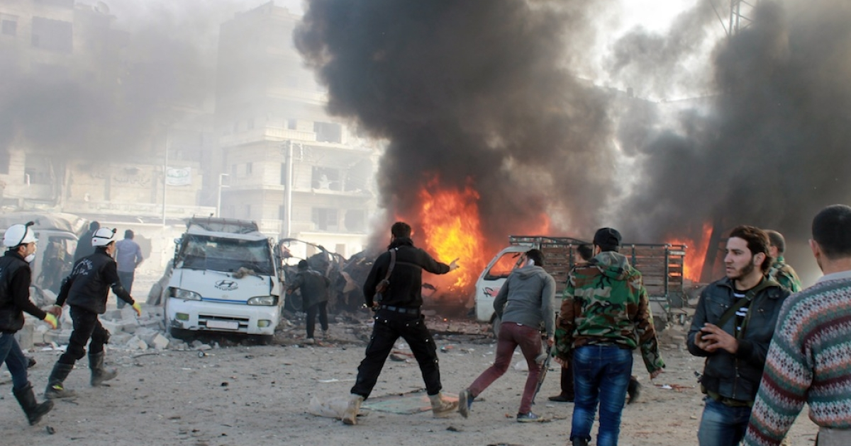 This photo taken on Jan. 21, 2014 – the day before the Syria peace talks opened in Switzerland – shows Syrian emergency workers and civilians at the scene of a bombing in the northern city of Aleppo. Government forces reportedly dropped a barrel bomb on a minibus carrying civilians.</p>