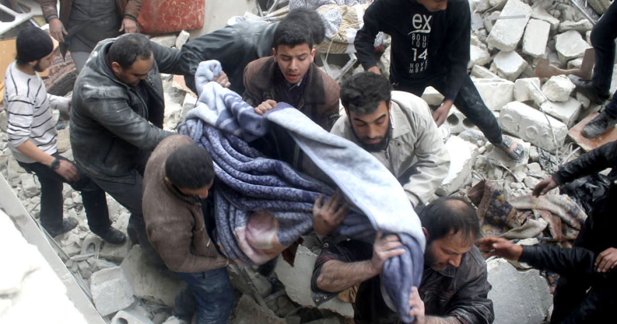 The body of a victim is pulled out of the rubble as people search for survivors after a building fell down following reported air raids by government warplanes on January 19, 2014 in the northern Syrian city of Aleppo.</p>