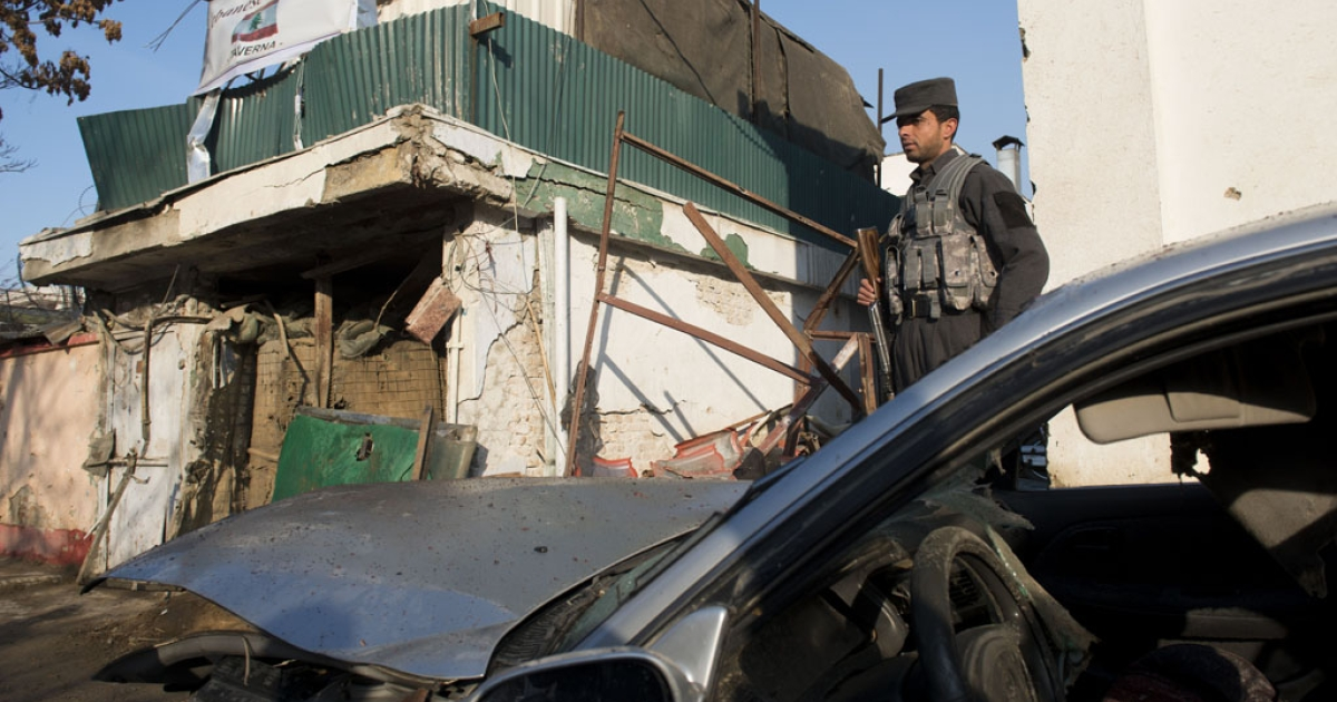 An Afghan policeman stands next to Taverna, a Lebanese restaurant, that was attacked in Kabul, on Jan. 18, 2014.</p>
