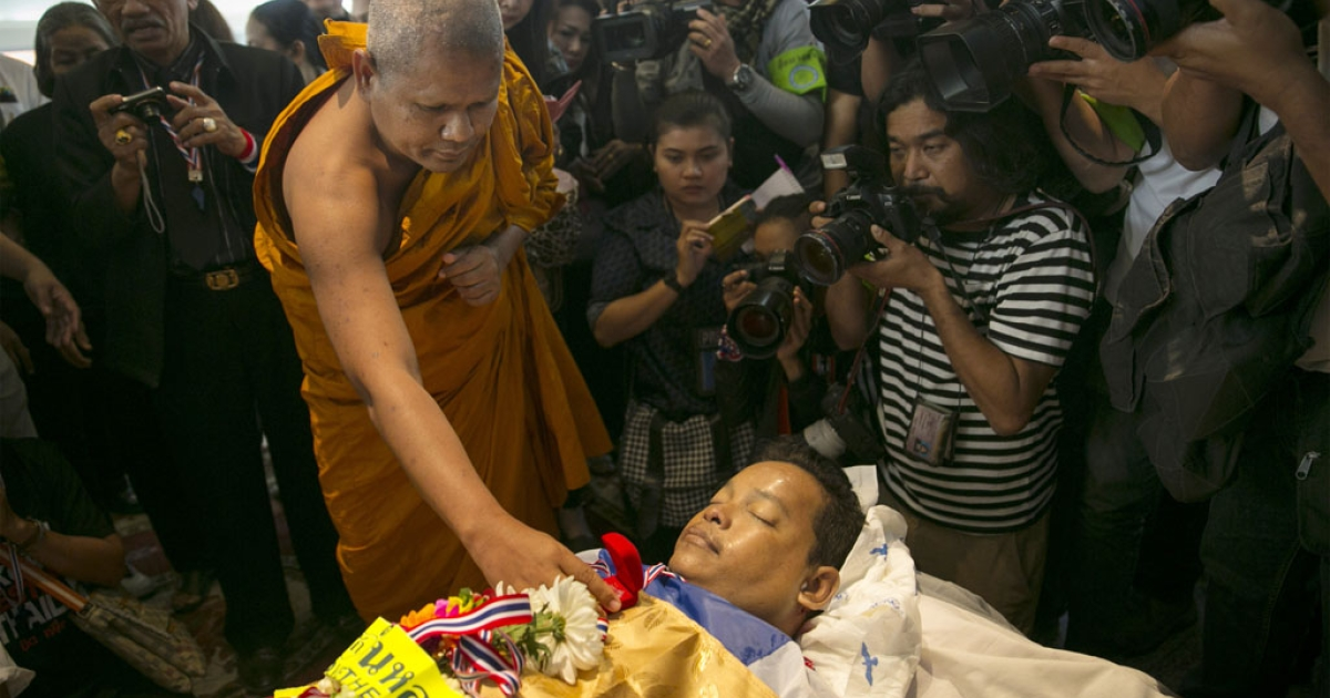 A Thai monk touches the body of Prakong Choochan saying a prayer during a memorial service Jan. 19, 2014 in Bangkok, Thailand. Prakong was an anti-government protester who was killed when a grenade was thrown during a march.</p>