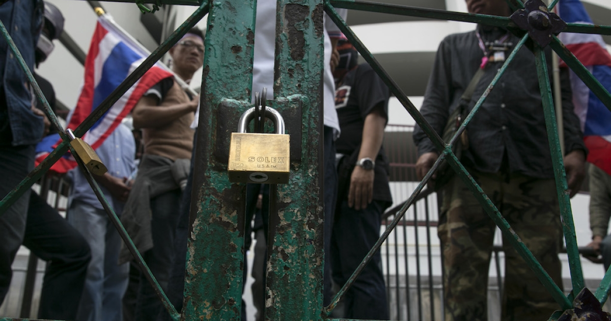 Protesters linger outside a locked polling station gate. Advance voting for the February 2nd general elections was unable to continue because the protesters blocked the station on Jan. 26, 2014 in Bangkok. The anti-government protesters vowed to stop all elections from taking place in the capitol city.</p>