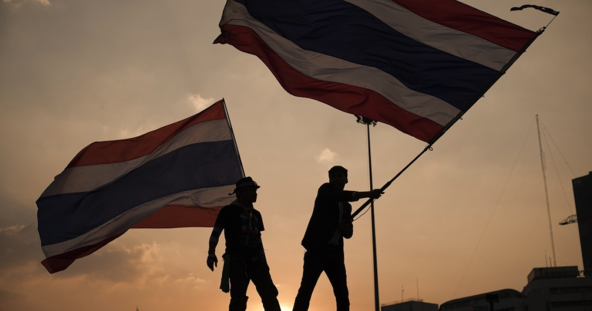 Anti-government protesters wave a flag in the pre-dawn hours in Bangkok on Jan. 15, 2014.</p>