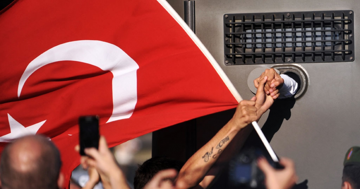 An Ergenekon prisoner being driven in a police armoured vehicle holds a protestor's hand on August 5, 2013, as police block access to a courthouse near Istanbul. The prisoner was one of 275 people accused of plotting to overturn the Islamic-leaning government.</p>